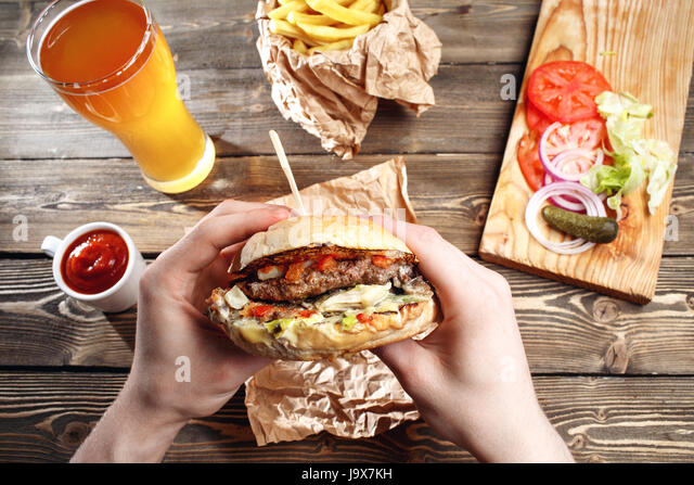 Hands holding fresh delicious burgers with french fries, sauce and beer on the wooden table top view. - Stock Image