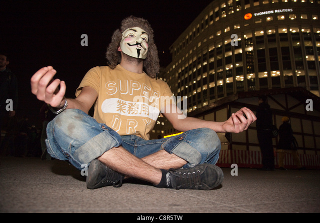 31 October 2011, London, UK. Meditating at Canary Wharf. On Halloween, Masked UK Uncut protesters and Zombie Bankers - Stock Image