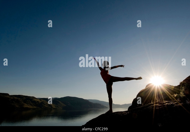 A silouetted female dancer trains over Kamloops lake at sunset, Kamloops, British Columbia Canada - Stock Image