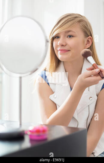 Girl applying makeup in front of mirror at home - Stock Image