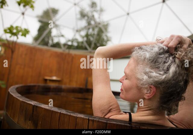 Mature woman with hands in hair in hot tub at eco retreat - Stock Image