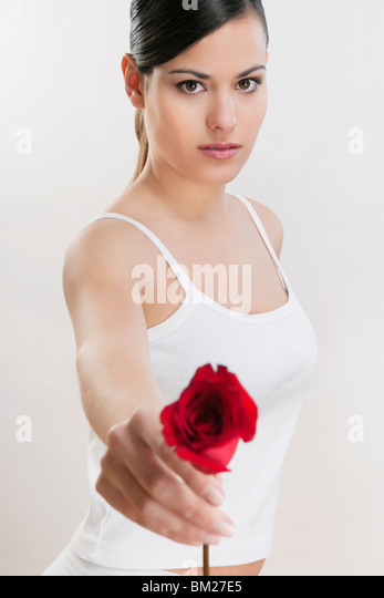 Portrait of a woman holding a rose - Stock Image