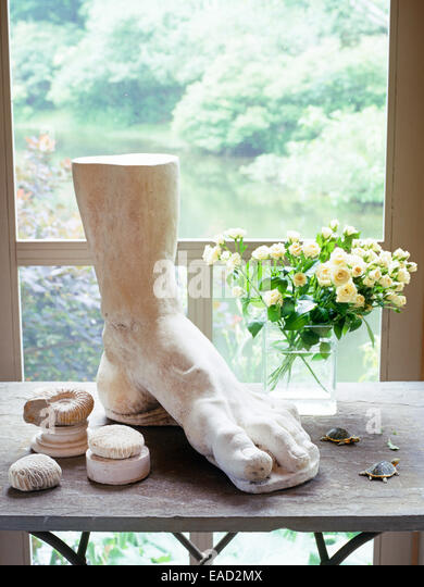 decor on side table in screened in porch of country house - Stock Image