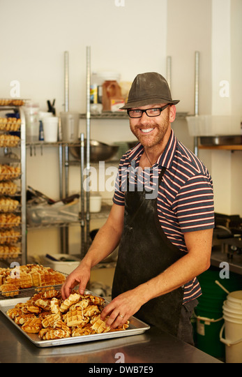 Male baker with tray of waffles in bakery - Stock Image
