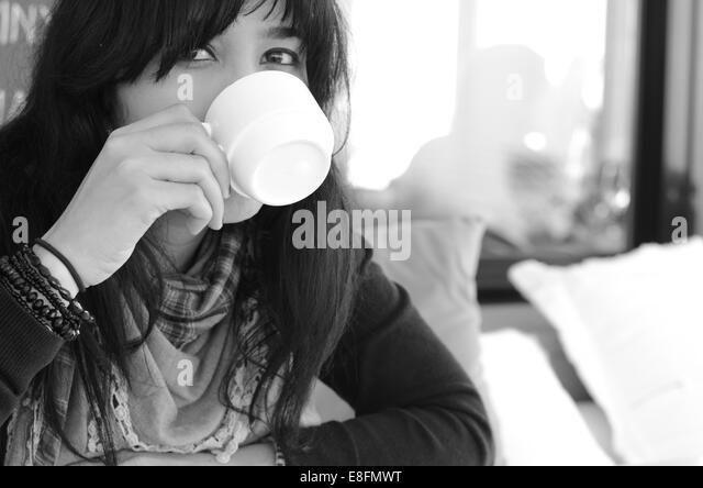 Portrait of woman drinking coffee in room - Stock-Bilder