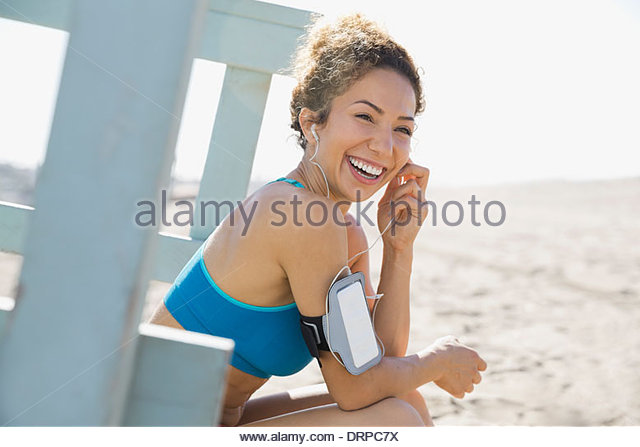 Active woman putting ear buds in before workout - Stock Image