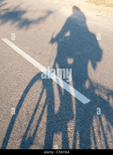 Man riding bicycle shadow on a road - Stock Image