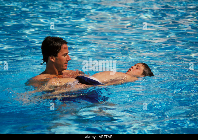 A father teaches his nine year old son to float - Stock Image