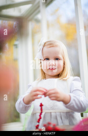 Girl (2-3) stringing beads in house - Stock Image