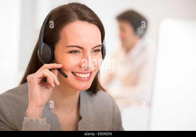 smiling Female pretty desk headphone portrait - Stock Image