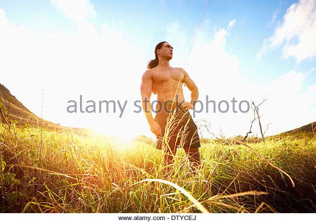 Hawaiian man standing in rural field - Stock Image