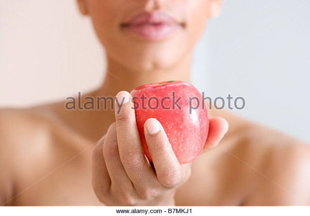 A woman holding a red apple - Stock Image