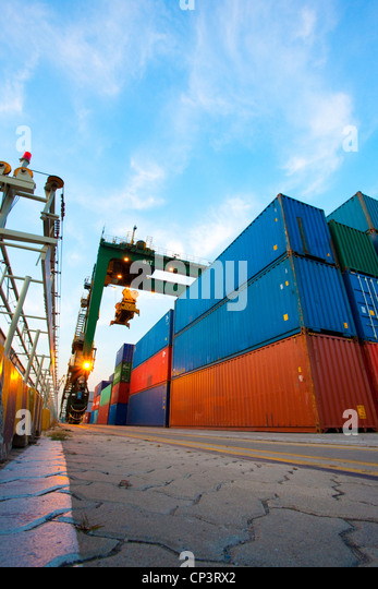 Cranes and multi-colored stack of cargo containers at dusk - Stock Image