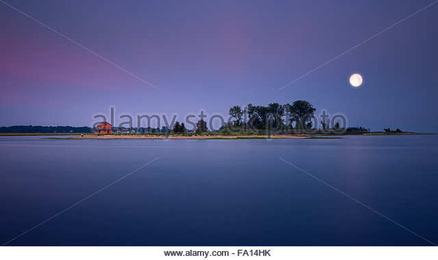 Guilford Grass Island with its iconic red hut during dusk with the moon reflecting on the water and the ocean a - Stock Image