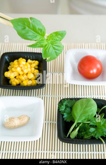 Chopsticks holding sprig of herb over several dishes of food - Stock Image