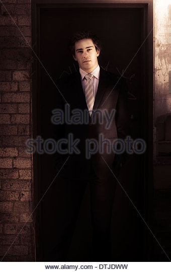 Good Old Fashioned Customer Service Concept With A Male Vintage Waiter Standing In The Dark Doorway Of A Restaurant - Stock Image