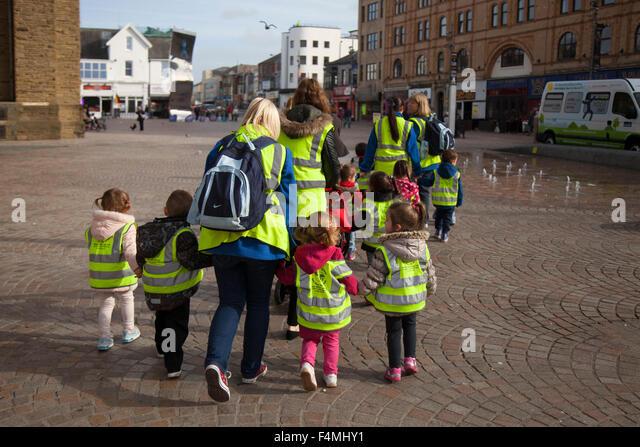 Safeguarding Pre-School children wearing protective fluorescent hi-vis hazard jackets on walk around Blackpool with - Stock Image