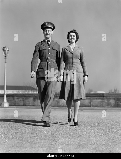 1940s SMILING COUPLE WALKING FORWARD MAN IN ARMY UNIFORM - Stock Image