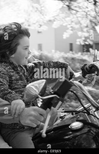 Boy on motorcycle with dad - Stock-Bilder