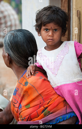 Indian toddler leaning on her grandmother in the doorway of there house in a rural indian village - Stock Image