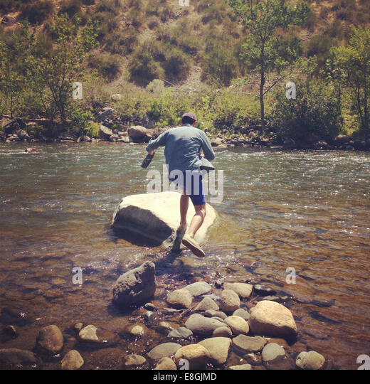 Man jumping across rocks in river - Stock Image