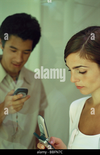 Young woman looking at cell phone, man in background lookng at own phone, smiling - Stock-Bilder
