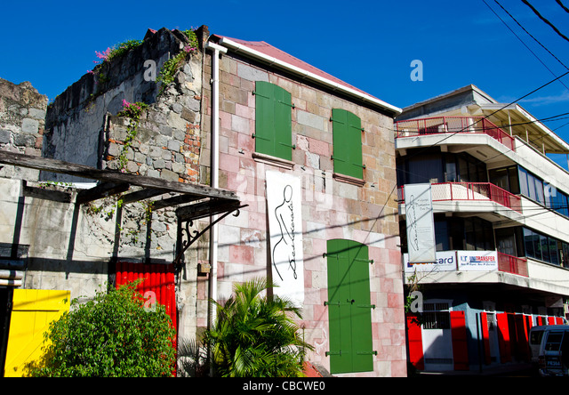 Roseau Dominica old plain colonial French Style warehouse next to modern building - Stock Image