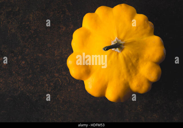 Yellow fresh pattypan squash on the rusty metal background top view - Stock Image