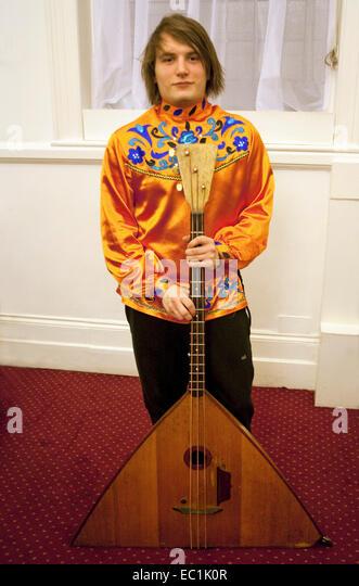 Bass balalaika. The balalaika  is a Russian folk stringed musical instrument with a characteristic triangular body - Stock Image