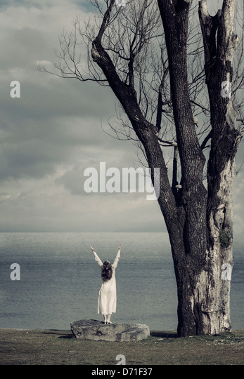 a girl in a white dress is standing on a stone at the sea - Stock Image