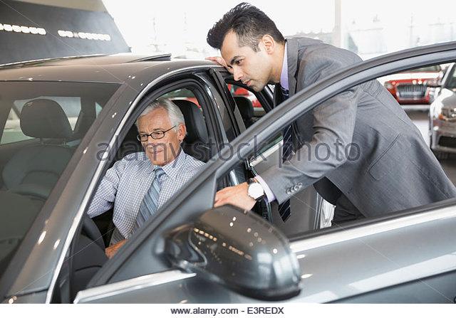 Salesman and man looking inside car in showroom - Stock Image