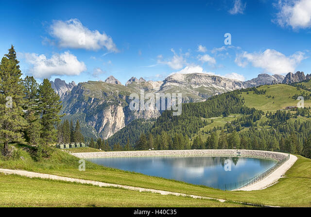 artificial lake in the mountains with blue sky in the background in summer season - Stock Image