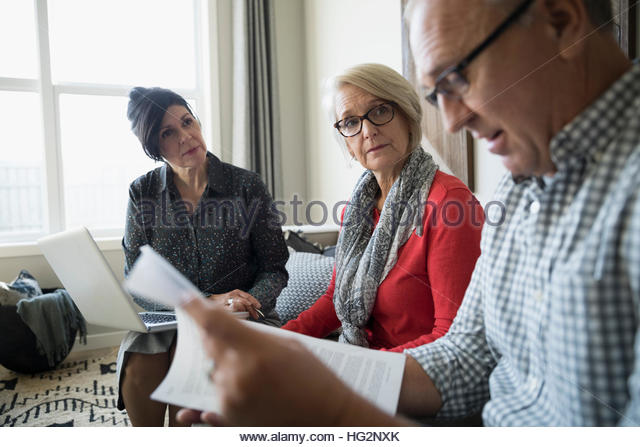 Financial advisor with laptop and paperwork meeting with senior couple in living room - Stock Image