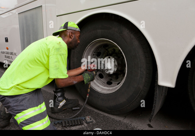 Mechanic removing a bus wheel with an impact wrench - Stock Image
