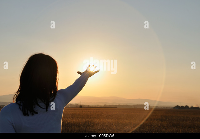 Young woman reaching for sun - Stock Image