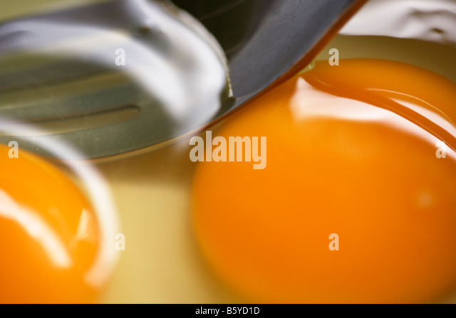 Egg yolk and fork close up - Stock Image