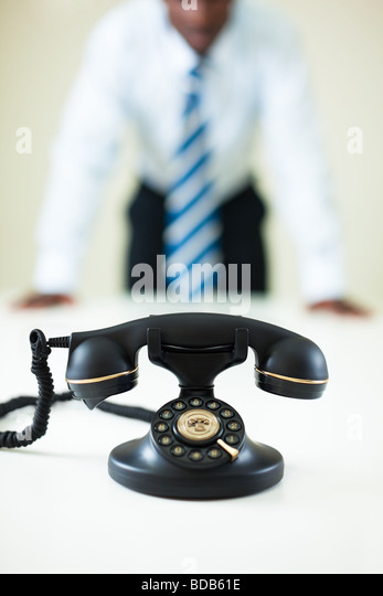afro american businessman waiting for a call. Selective focus on telephone - Stock Image