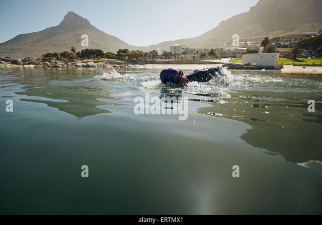 Male athlete swimming in open water. Athlete practicing for the triathlon competition. - Stock Image