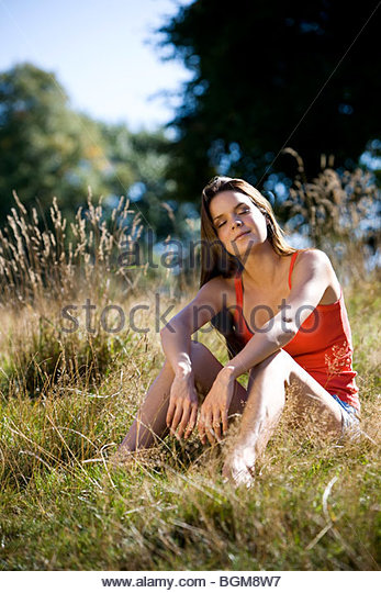 A young woman sitting on the grass, enjoying the sunshine - Stock Image