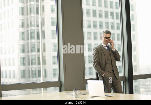 Portrait of businessman in high rise office - Stock Image
