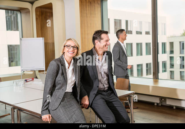 Businesspeople sitting on conference table - Stock-Bilder