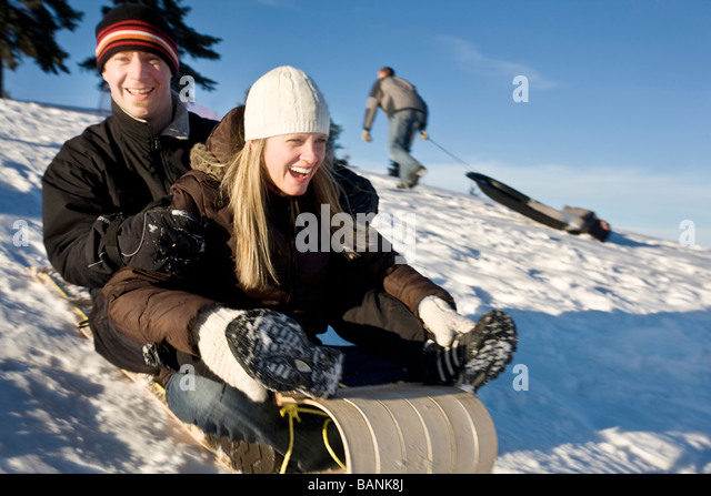 Winter sports; Couple tobogganing down a hill - Stock Image