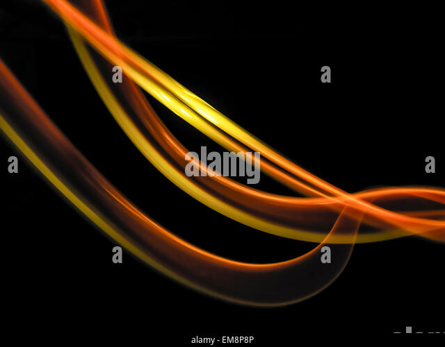 Abstract light trails made by molten metal against black background - Stock Image