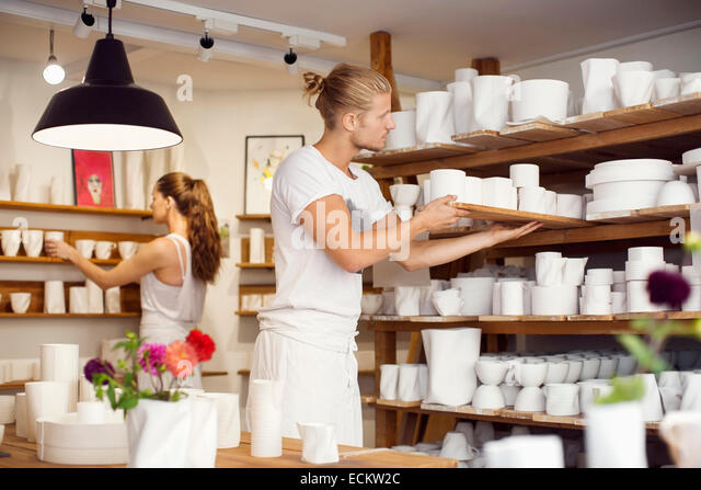 Workers arranging craft products at crockery workshop - Stock Image