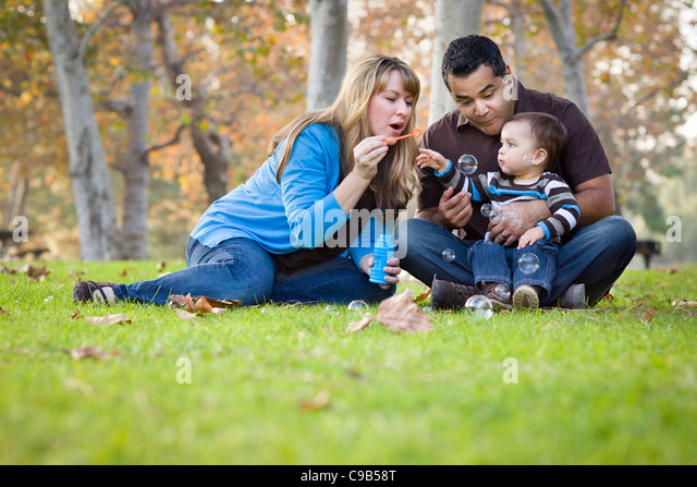 Happy Young Mixed Race Ethnic Family Playing with Bubbles In The Park. - Stock-Bilder