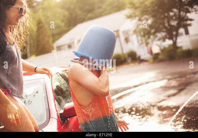 Young man with bucket covering head - Stock-Bilder