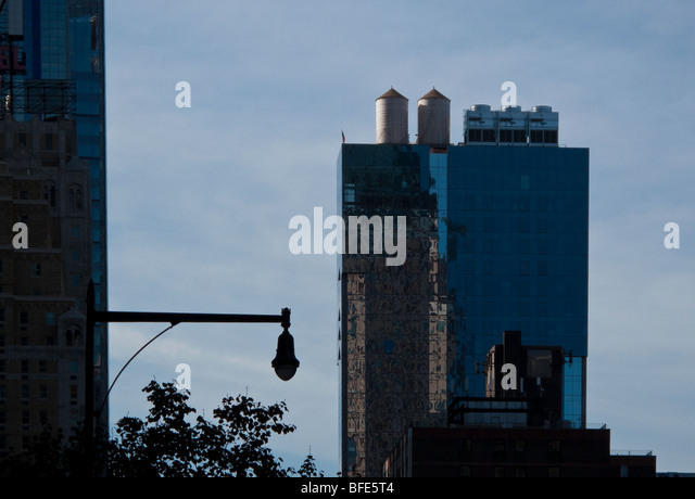 Water tanks an ever present sight in New York City, stand out atop a high rise building in the City. - Stock Image