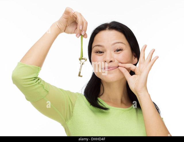 Woman locked mouth with key on white - Stock Image