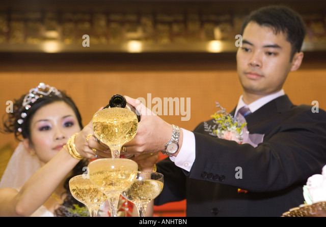 Bride and groom pouring champagne into stacked champagne glasses together - Stock Image