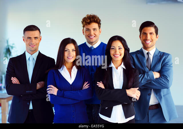 Group of a happy co-workers standing with arms folded in office - Stock Image